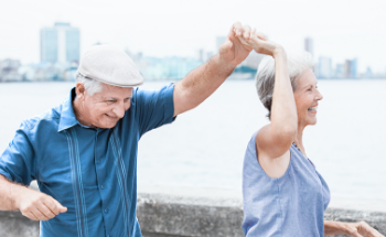 Older man and woman dancing and having fun outside near the sea with a city in the background.